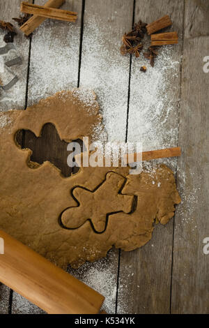 Directly above shot of dough with pastry cutter and rolling pin on wooden table - Stock Photo