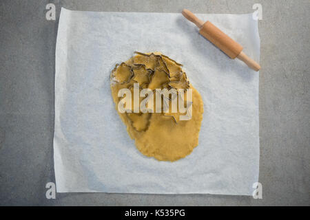 Directly above shot of various shape pastry cutter on rolled dough on wax paper - Stock Photo
