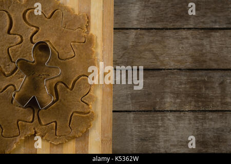 Directly above shot of gingerbread man pastry cutter on dough over cutting board - Stock Photo