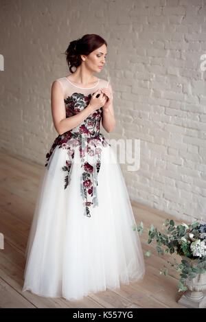 Full-length portrait of Beautiful luxurious female model with medium brown hair in a long fashinable dress standing - Stock Photo
