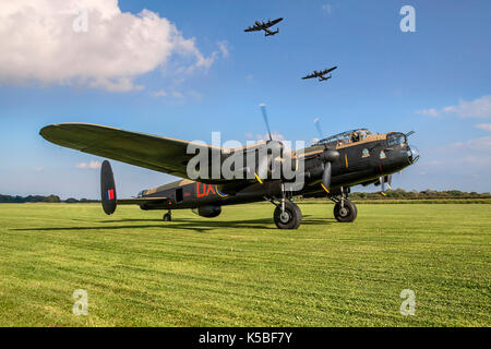 Lancasters 'City of Lincoln' and 'Vera' fly over 'Just Jane' at East Kirkby. - Stock Photo