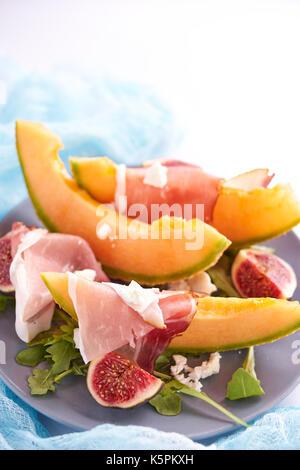 Ripe sweet melon with prosciutto, figgs and arugula - Stock Photo