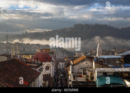 Dramatic sky and early morning mist rolling into a valley in the Historic Center, downtown Quito, capital city of - Stock Photo
