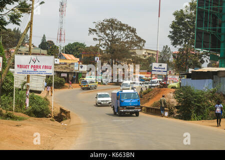 Vehicles on road through small town as people walk on roadside, Kenya - Stock Photo