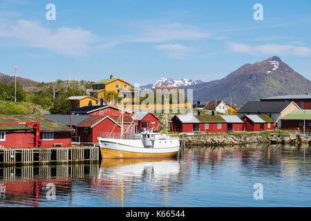 Boat moored in harbour with typical Norwegian Rorbu huts in fishing village. Ballstad, Vestvågøya island, Lofoten - Stock Photo