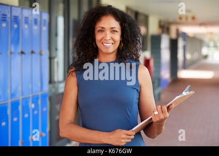 Middle aged black female teacher smiling in school corridor - Stock Photo