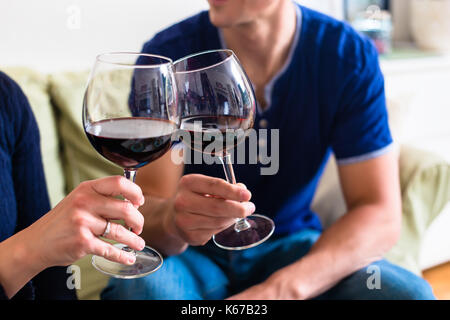 Romantic young couple toasting with red wine while sitting on th - Stock Photo