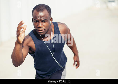 athlete running in the park - afro-american runner training and jogging on a summer day outdoors wearing blue color - Stock Photo