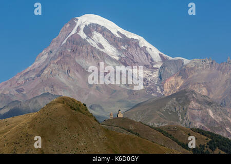 View looking up from the town of Kazbegi in Georgia, showing Gergeti Trinity Church Monastery and the peak of Mount - Stock Photo