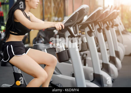 Sportive Woman during cycling workout in sport gym bike doing cardio exercise. - Stock Photo