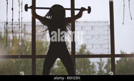 Girl in the gym lifting up the barbell - silhouette - Stock Photo