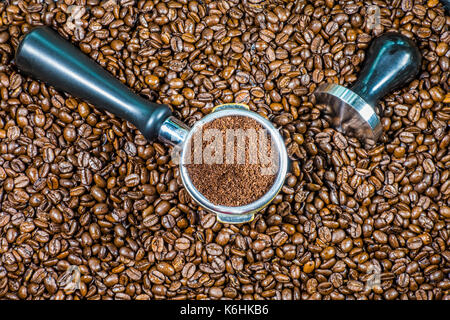 Espresso making concept: Ground coffee in an espresso machine portafilter basket, with steel tamper alongside, on - Stock Photo