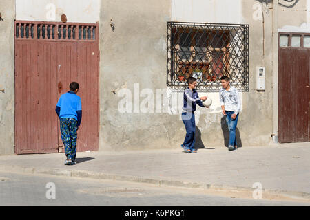 Essaouira, Morocco - December 31, 2016: Children playing with ball on the street in medina - Stock Photo