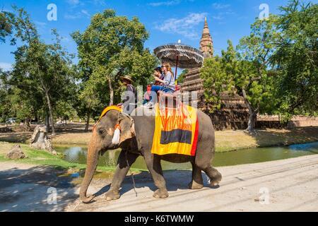 Thailand, province of Phra Nakhon Si Ayutthaya, Ayutthaya, tourist walk on the back of elephants among the ruins - Stock Photo