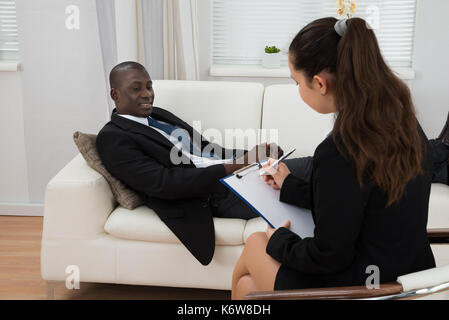 Young African Patient On Couch In Front Of Female Psychiatrist Taking Notes - Stock Photo