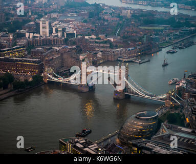 View of opened and illuminated Tower Bridge across the River Thames, with London City Hall, evening, London, England - Stock Photo