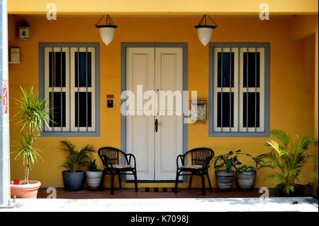 Ground floor view of traditional shop house with door, windows, Dutch lamps and garden furniture in Everton Park, - Stock Photo