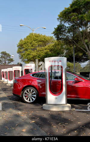 Tesla 'S' sedan connected to 480 volt (fast charging) Supercharger Station. - Stock Photo