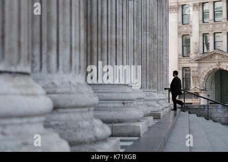 Man in a black suit walking up the stairs and entering through the west front colonnade into the Saint Paul's Cathedral, - Stock Photo