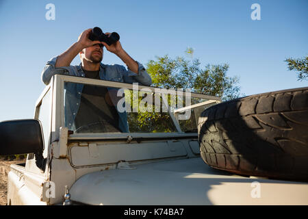 Young man looking through binoculars standing in off road vehicle against clear sky - Stock Photo