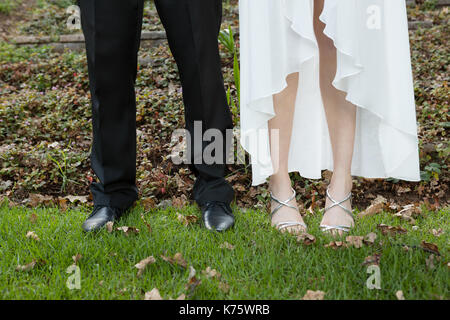 Low section of newlywed couple standing on grassy field - Stock Photo