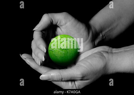 female hands holding a green earth, environment protection and earth's   day concept - Stock Photo
