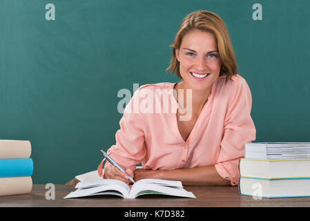 Young Happy Female Teacher Studying At Desk In Classroom - Stock Photo