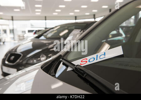 sign sold in various languages under the windscreen wiper of a sold car in the showroom of a car sales company - Stock Photo