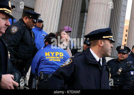 NYPD officers arrest a young woman as she attempts to stand on the steps of the New York County Supreme Court at - Stock Photo