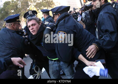 NYPD officers arrest a young an as he refuses to vacate the sidewalk outside the New York County Supreme Court at - Stock Photo