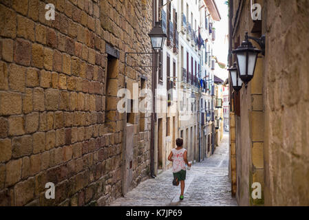 Boy running through the alleyways of old town Hondarribia, in Basque Country, Spain - Stock Photo