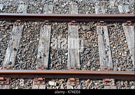 Old timber sleepers supporting steel rails on a little used part of the railway system - Stock Photo