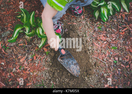 A little girl digs with a spade in a garden. - Stock Photo