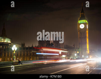 Palace of Westminster with Big Ben at night, red double-decker bus on the Westminster Bridge, motion blur, London, - Stock Photo