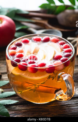 Herbs and spices infused warming tea for cold winter days in glass cup. Closeup, vertical - Stock Photo