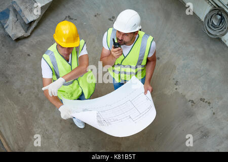 Construction Workers Wrapped up in Discussion - Stock Photo