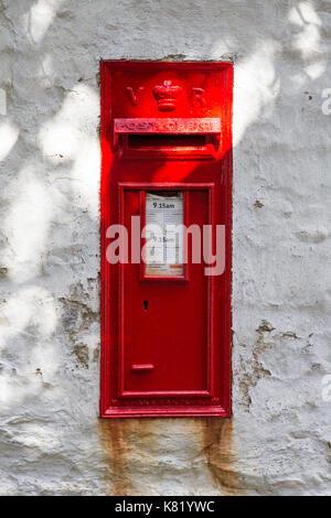 Red Post box set into white wall, UK. - Stock Photo