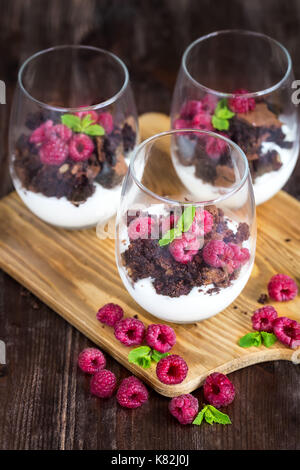 Raspberry and chocolate trifle desert on wooden background - Stock Photo