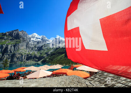 Tourists relaxing at Lake  Oeschinensee Bernese Oberland Kandersteg Canton of Bern Switzerland Europe - Stock Photo