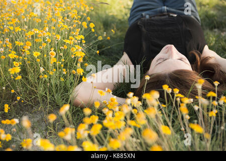 A woman in a black vest top and jeans lying on the grass with her hands behind her head. - Stock Photo