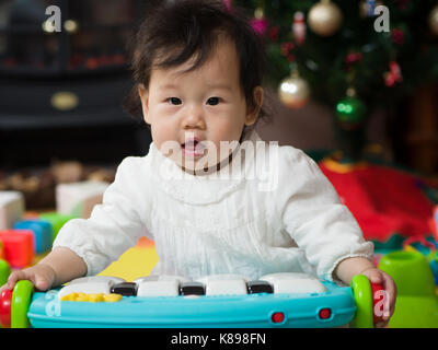 Asian baby girl playing piano toy in home - Stock Photo