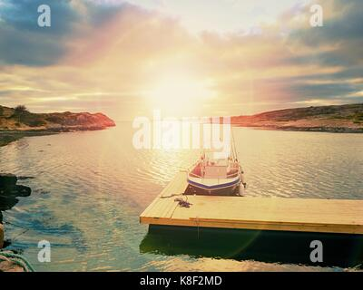 Fishing boat in bay port, sunset calm water. A motorboat for sport fishing tied to a wooden floating dock. - Stock Photo