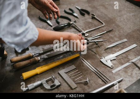 Hands of female jeweller laying out hand tools at workbench in jewellery workshop - Stock Photo