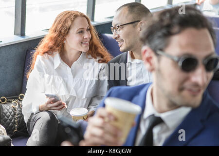 Businessman and woman chatting on passenger ferry - Stock Photo
