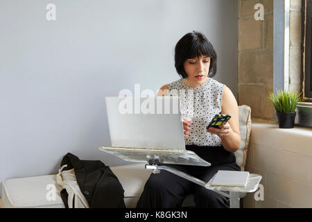 Woman sitting using laptop on laptop stand, holding smartphone - Stock Photo