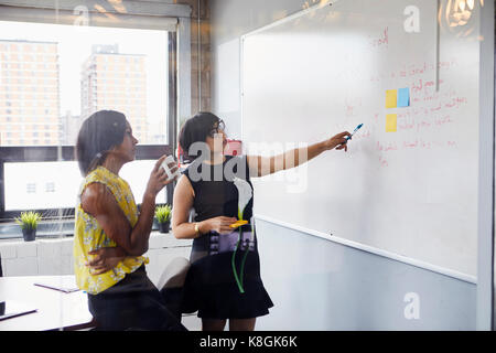 Two women in office, solving problem, using whiteboard, sticky notes stuck on whiteboard - Stock Photo