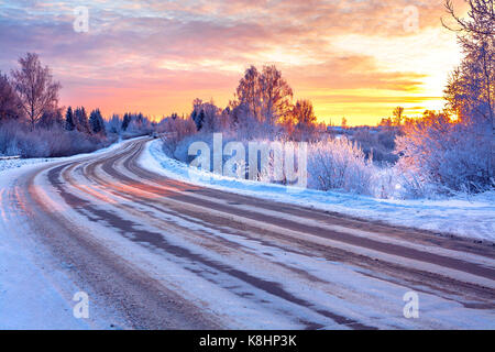 winter landscape with sunset,road and forest. path winter covered with snow in rays of sunset. wintry snowy road - Stock Photo
