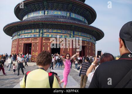 A woman poses for a photograph outside the Temple of Heaven in Beijing, a popular tourist spot for both Chinese - Stock Photo