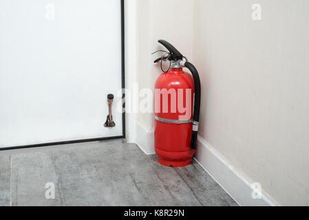 Fire extinguishers in home door. - Stock Photo