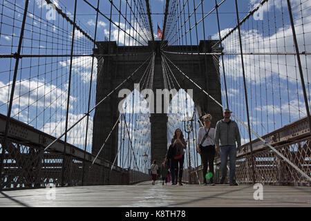 New York, NY, USA - May 3, 2017: Worms eye view of people walking to Manhattan across the Brooklyn Bridge on a sunny - Stock Photo